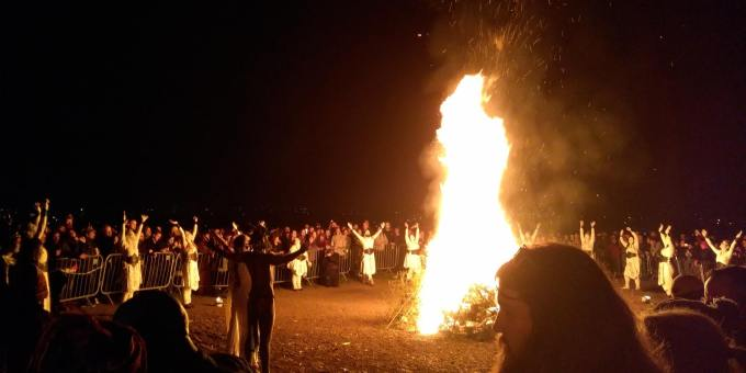 """Bonfire at the Beltane Fire Festival 2019, Calton Hill, Edinburgh. The reunited May Queen and Green Man face the fire, while dancers stop to raise their arms to heaven. Photo by """"Nyri0"""" This file is licensed under the Creative Commons Attribution-Share Alike 4.0 International license."""