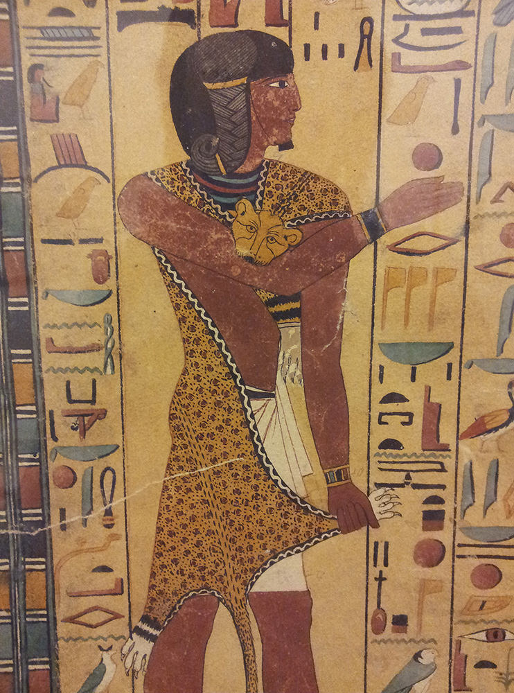 A priest wearing a leopard skin, surrounded by colourful hieroglyphs