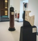 Two freestanding artefacts on pedestals - one is a carved stone head of a king, the other a carved limestone stela with the top corner broken off