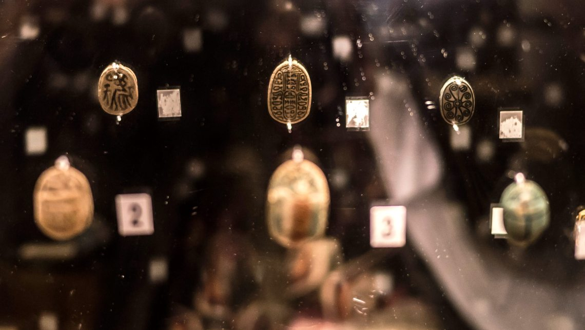Three small scarab-shaped amulets mounted on a mirror, showing reflections of the backs, which have spiral patterns, stick figures and hieroglyphs
