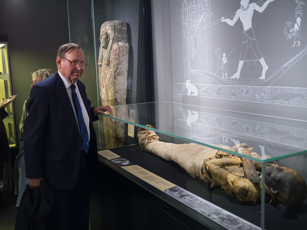 An older man in a smart suit standing and looking at an Egyptian mummy in a glass case