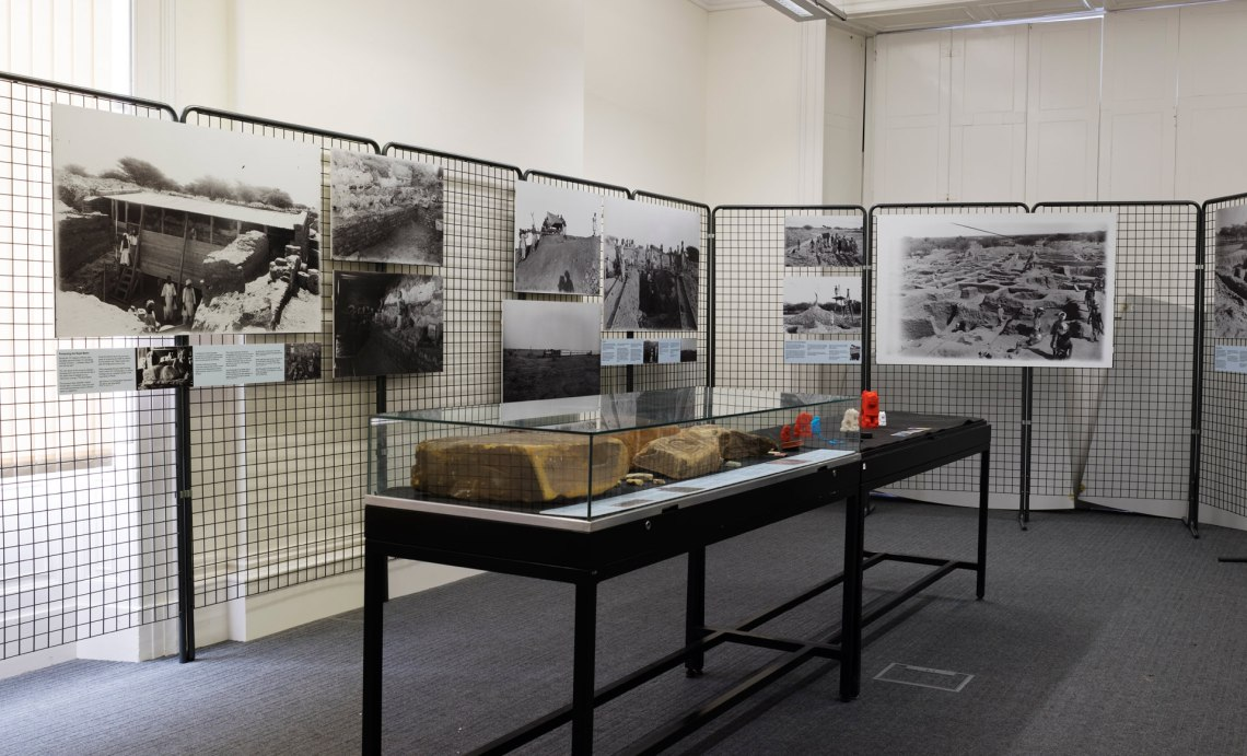 Looking diagonally across the room. The back and left walls are included, which have tall, metal gridded stands to which large reproductions of the excavation photos are attached. In the middle of the room stands a table-sized display case with artefacts inside. Just behind the case is another stand without its glass top with colourful 3D prints of artefacts on top