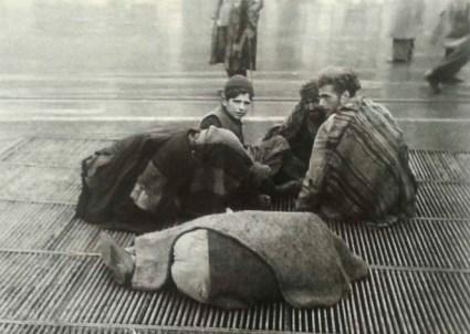 Εξαθλιωμένοι άνθρωποι 1941-1942. Προσπαθούν να ζεσταθούν καθισμένοι πάνω στις σχάρες, ίσως του Ηλεκτρικού της Ομόνοιας, που έβγαζαν ζέστη.