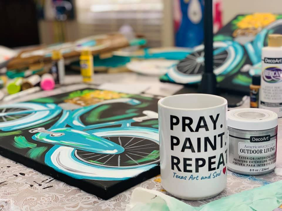 "mug that says ""pray, paint, repeat"" in front of a table filled with art supplies including a painted canvas"