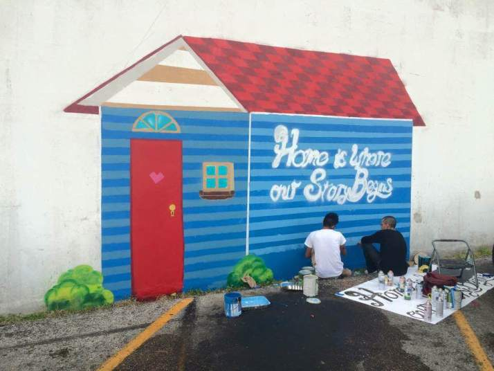 Josué and Esteban work to complete the mural.