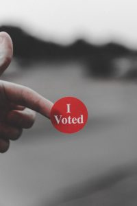 """Picture of a finger with an """"I voted"""" sticker on it. It aligns with the theme of politics at work because people will often wear I voted stickers."""