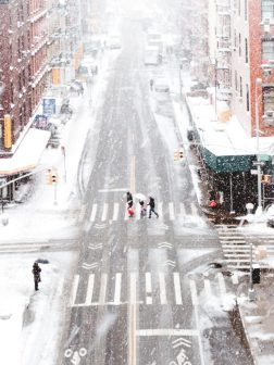 People walking over a snow covered street to show that the weather affects employees ability to travel