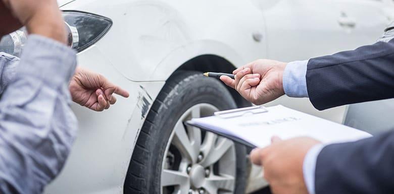 insurance adjuster inspecting car damage