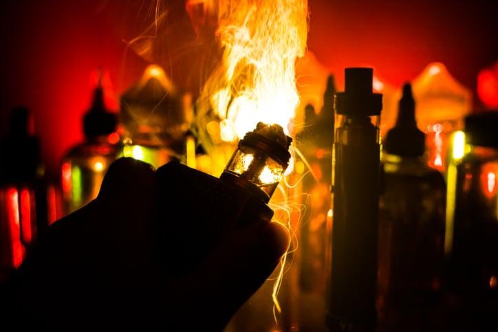 Electronic Cigarette vape explosion. Smoke clouds and vape liquid bottles on dark background. Light effects.