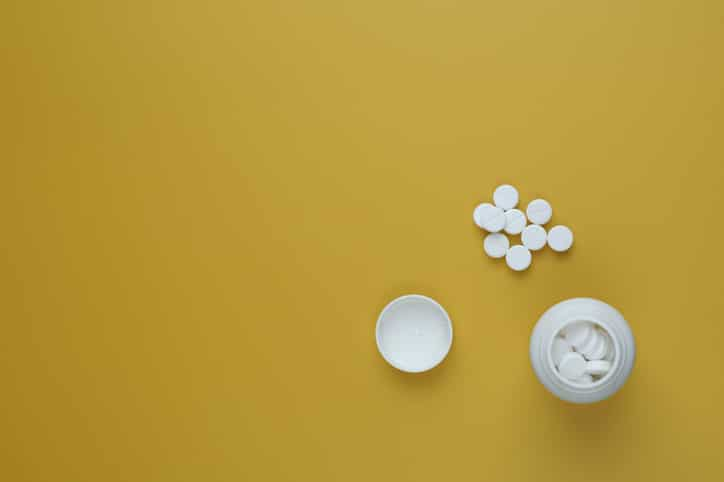 Pill bottle spilling pills on to surface isolated on a yellow background. Copy space. Flat lay.