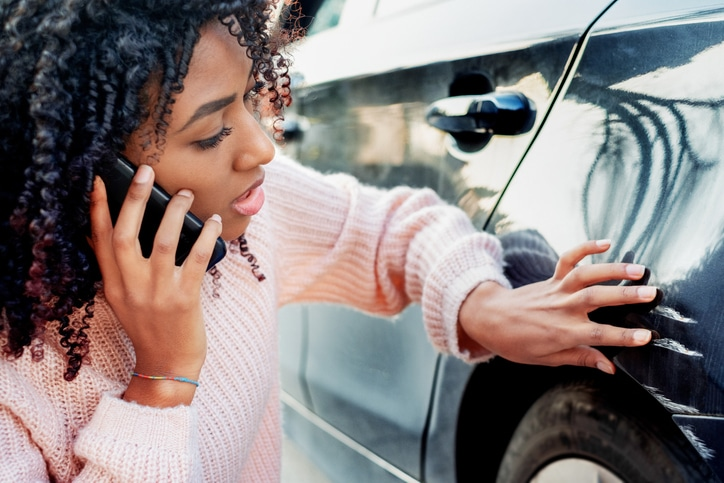 Black woman feeling sad after scratching her auto
