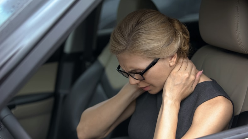 women with hurt neck in car