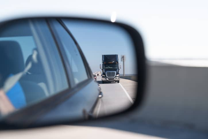 truck in side view mirror on car
