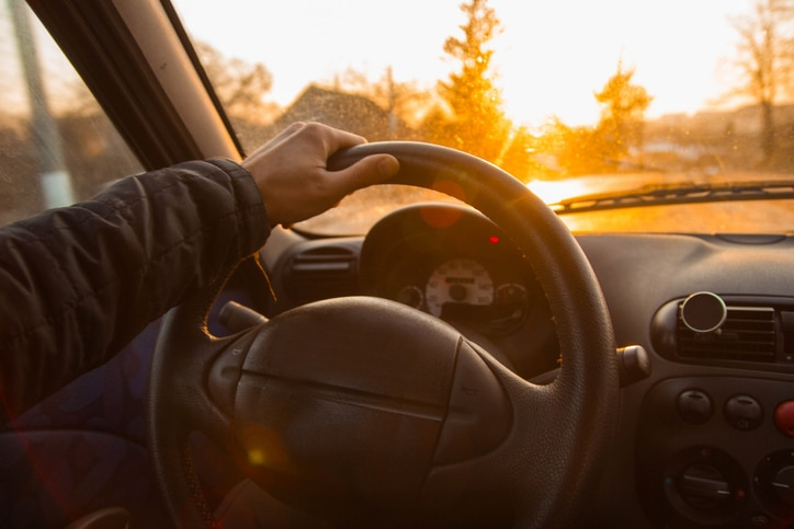 man holding steering wheel