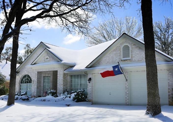 house with snow and Texas flag