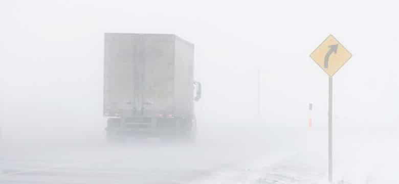 Semi truck driving in snow storm image