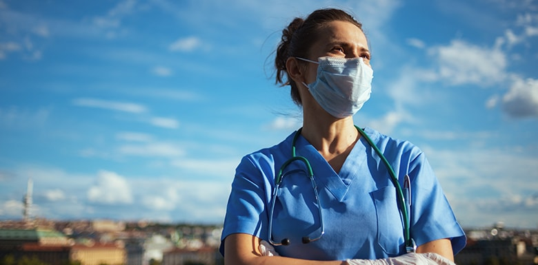 Female doctor wearing mask in front of blue sky