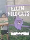 """Happy young boy holding a big veggie box. He is standing in front of a sign for Elgin Wildcats. """"I can't wait to make a salad1 I love salad!"""""""