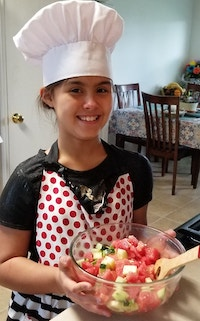 Elgin student wearing chef's hat with the beautiful salad she made.