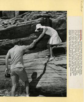Senator Kennedy helping his wife, Ethel, down a sandstone formation.
