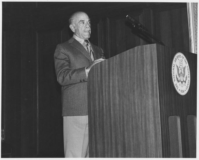 Image of Frank Capra standing at podium.