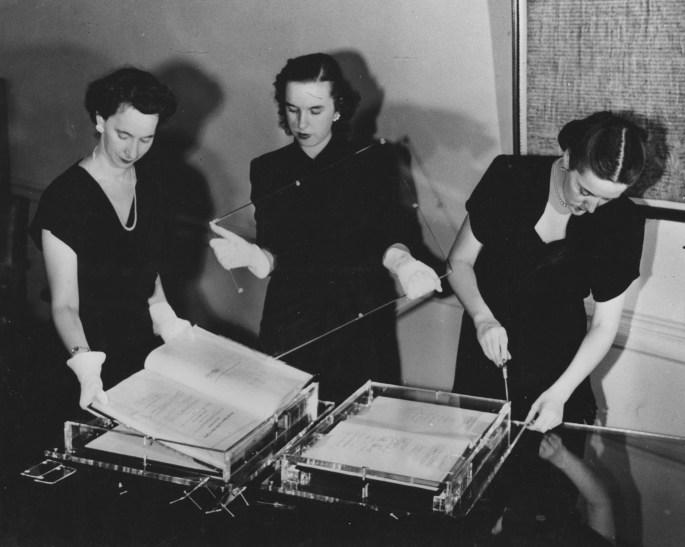 Three women working on exhibit cases.