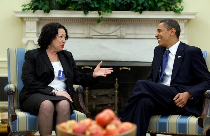 Obama and Sotomayor seated in chairs talking