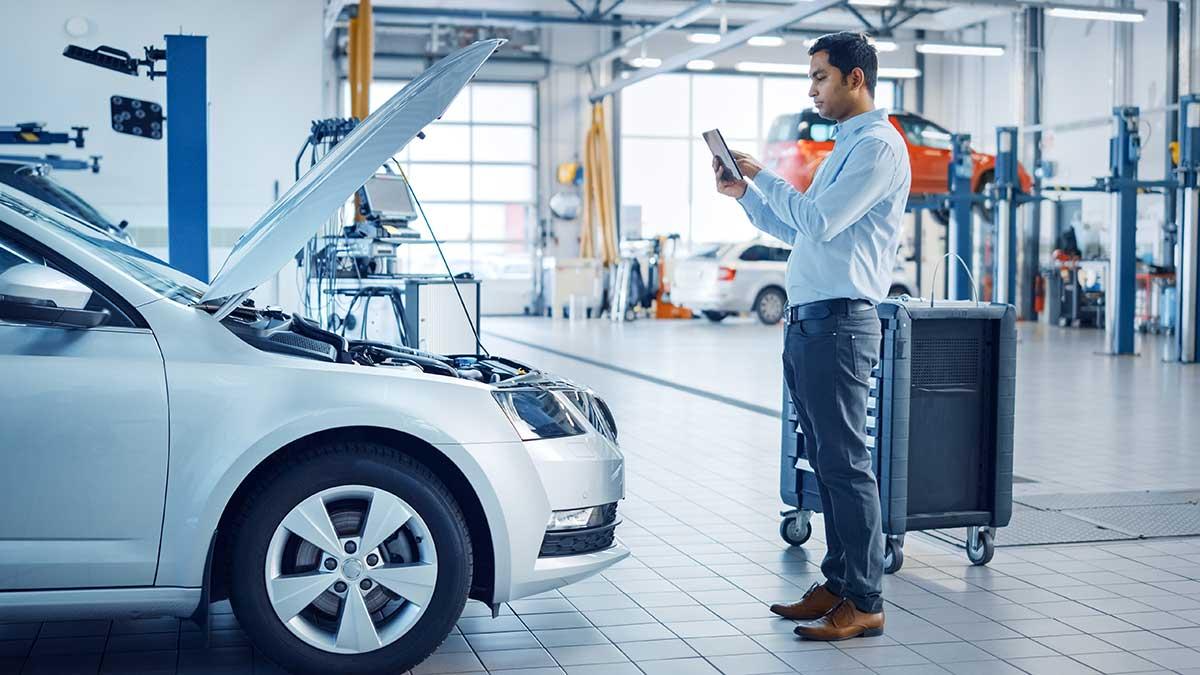 homme inspectant une voiture avec un mobile