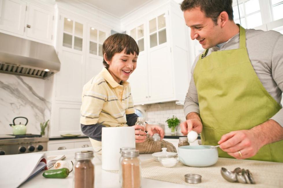 сын и отец готовят на кухне еду