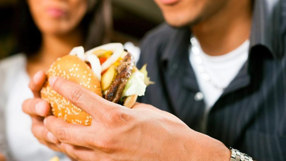 парень держит в руках гамбургер