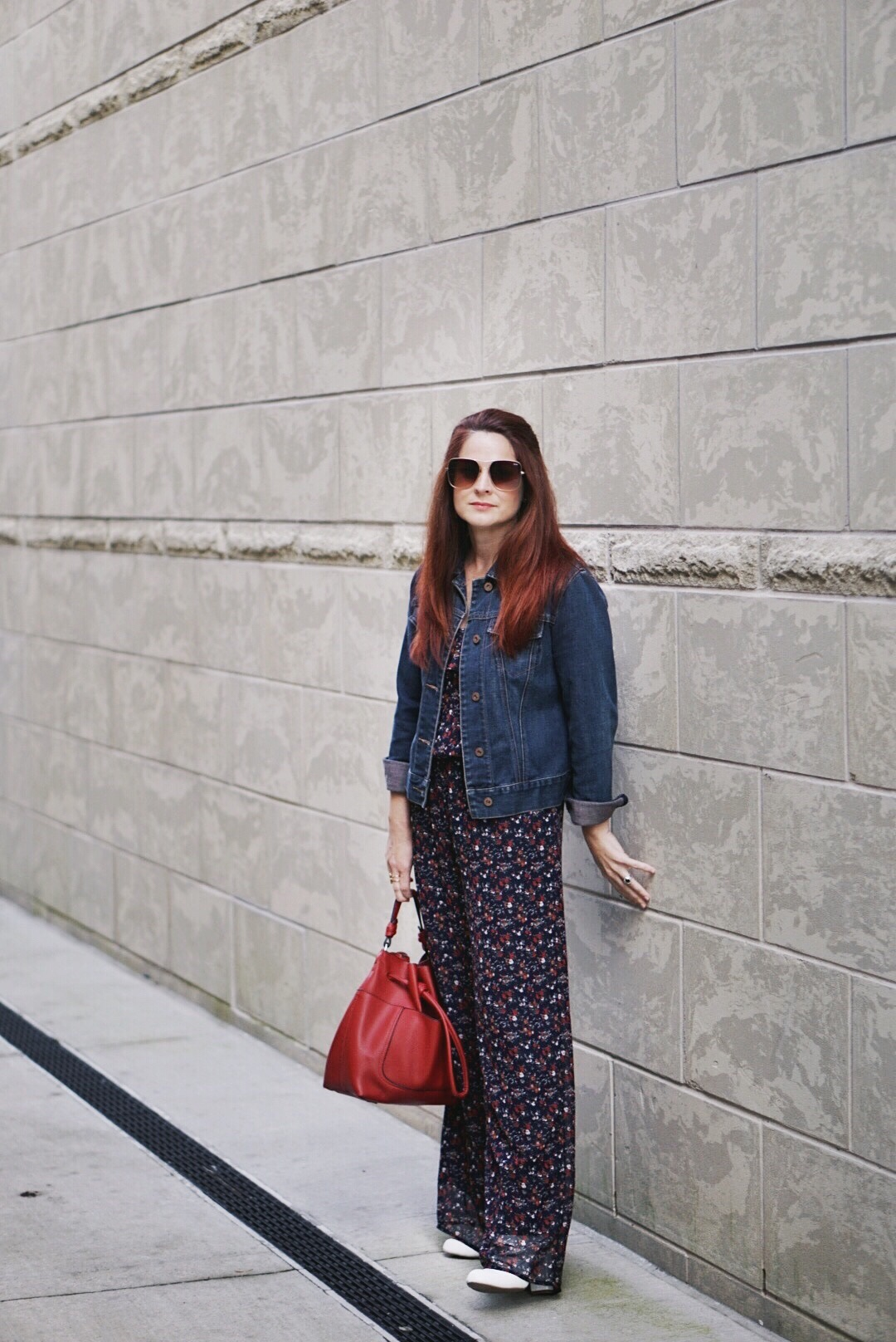 floral jumpsuit, denim jacket, red bucket bag, white boots, cutting back, pruning roses
