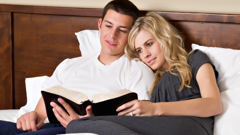 Couple reads the Bible in bed