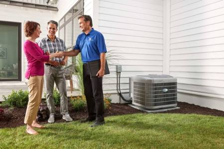 dealer discussing ac options with homeowners outside
