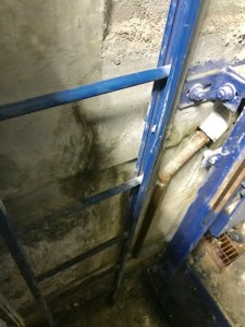 Evidence of water damage behind elevator pit ladder