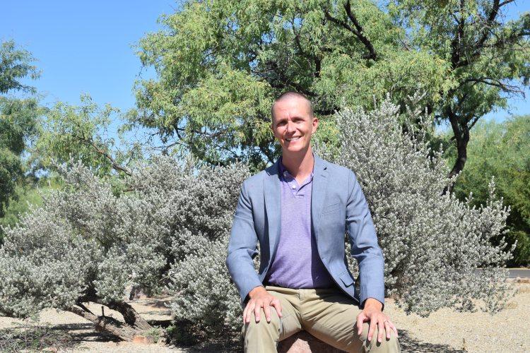 Man named Tim Grivois-Shah, seated on a boulder in front of desert landscape.
