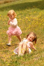 Foto retrato crianças brincando em meio as flores.