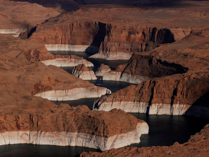 """In this aerial view, The tall bleached """"bathtub ring"""" is visible on the rocky banks of Lake Powell on June 24, 2021 in Page, Arizona."""