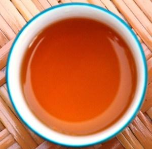 DMS Shi Er Black Pearls, Rot- und Bernsteinfärbung in weissem Tee-Becher
