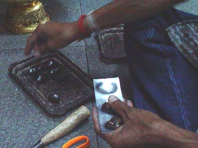 Devotee assists in Covering Bia Gae Amulets