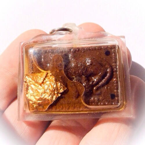 cat feeding a mouse sacred powder amulet, in sacred oils. this example is one of the Ongk Kroo Masterpiece Versions