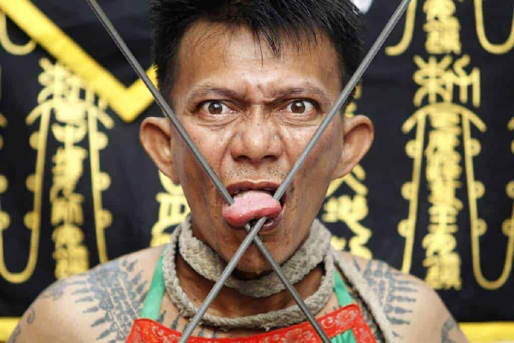 Men particpates in Sacred vegetarian festival. Thailand Event Guide