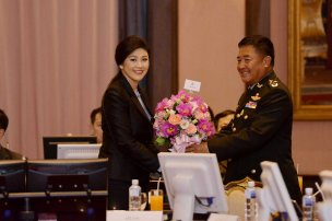 Yingluck receiving flowers from a senior officer of the Arm Forces