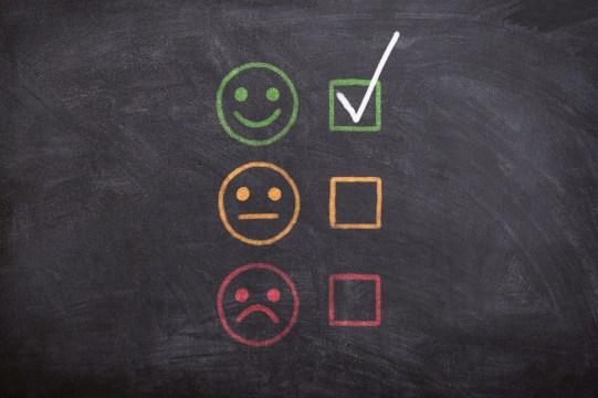 Imagem de um quadro negro, onde está desenhado três carinhas: uma com rosto feliz, neutro e triste.