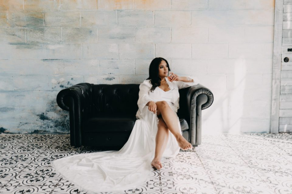 bride sitting on couch in bridal robe