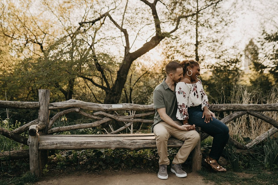 Woman sitting on man's lap on and and man nuzzling on shoulder of woman wooden bench