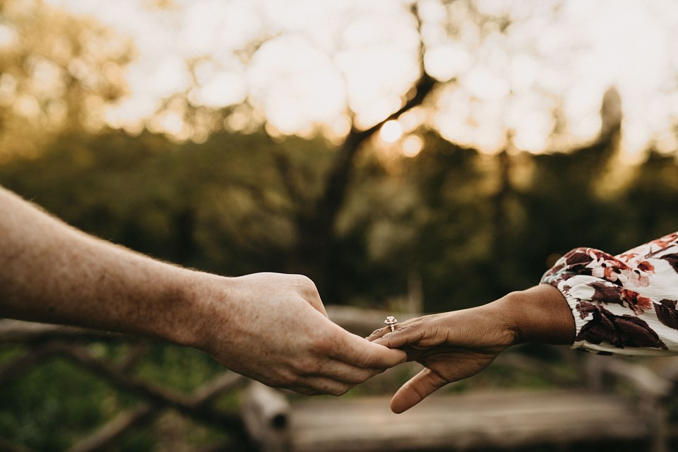 Closeup of couple extending hands to each other with engagement ring on