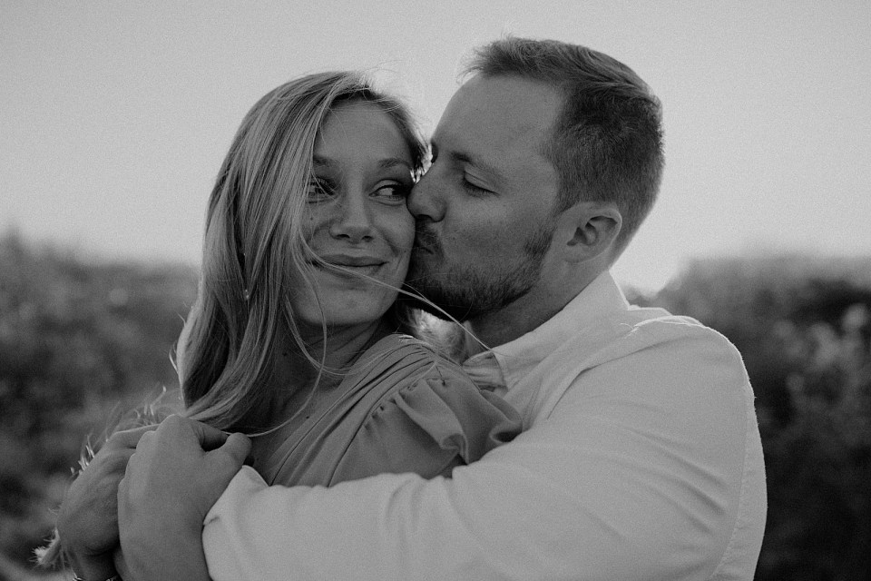 B&W man holding woman and kissing her on the cheek