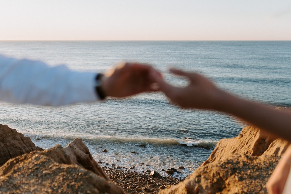 Shot of the ocean with blurry shot of Couple extending hands towards each other