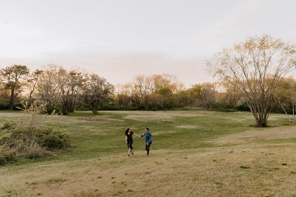 Wide shot of couple holding hands and running on the field together