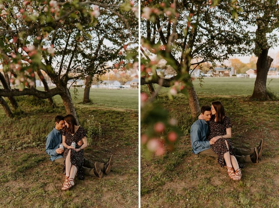 Woman sitting on man's lap with beer in hand underneath shade of tree